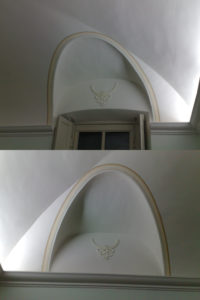 Decorazione ornamentale su arcata e dettaglio su stemma in gesso, applicato alla parete