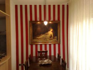 Decorazione e imbiancatura murale, linee verticali rosse e bianche per creare un effetto unico