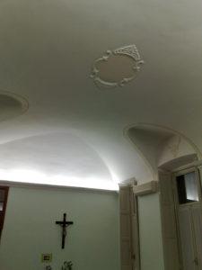 Dettaglio di decorazione ornamentale a corona, eseguito con uno stampo in gesso e applicato al soffitto